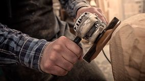Сarpenter saw sculpture. Close up of a carpenter, builder in work clothes saw to cut out sculpture from wooden a man`s head in the workshop, around a lot of Royalty Free Stock Photos