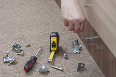 Close-up of carpenter hand tightens fixing screw, using key furn Royalty Free Stock Photo
