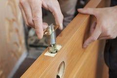 Close-up carpenter hands door lock installation. Installation locked interior door knobs, close-up woodworker hands install lock stock image