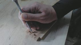 Close-up, carpenter making a dovetail on a wooden part with a chisel and hammer in a carpentry workshop.4k. 4k video. slow motion. Close-up, carpenter making a stock footage
