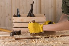 Close up of a carpenter planing a plank of wood with a hand plane stock photos