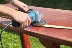 Close-up of carpenter`s hands working with electric sander - polishing old color from wooden table stock image