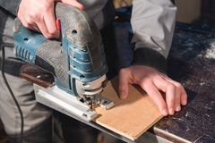 Close up of carpenter`s hands working power tools for processing wood. Power Jigsaw royalty free stock photo