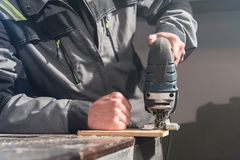 Close up of carpenter`s hands working power tools for processing wood. Power Jigsaw.  stock images