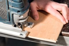 Close up of carpenter`s hands working power tools for processing wood. Power Jigsaw.  royalty free stock photo