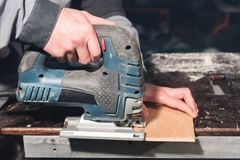 Close up of carpenter`s hands working power tools for processing wood. Power Jigsaw.  royalty free stock images