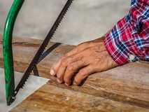 close up of Carpenter sawing a board with a hand wood saw. profession, carpentry, woodwork and people concept. stock photography