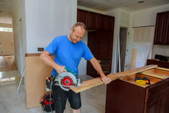 Close-up of carpenter using a circular saw to cut a large board of wood Royalty Free Stock Image