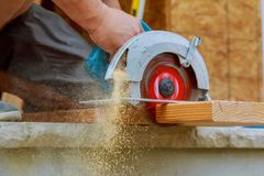 Close-up of a carpenter using a circular saw to cut a large board of wood royalty free stock image
