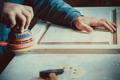 carpenter using sander for wood furniture Royalty Free Stock Photo