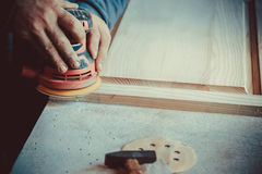 Close-up of carpenter using sander for wood furniture. Stock Photos