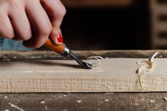 Close-up carpenter woman`s hand with a red manicure treats the tree, cuts the shavings. stock image
