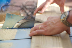Close-up of carpenter working with table saw Stock Images