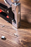 Close up carpentry stapler with staples on wood background Royalty Free Stock Photo