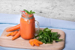 Close-up of carrot smoothie cocktail on a blue cloth background. A healthy detox beverage in a mason jar next to cut Stock Photography