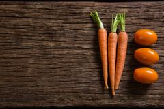 Carrots and tomatoes on wooden table Stock Photos