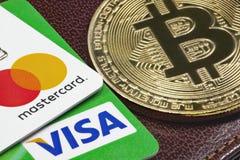 Close up cartões de crédito do visto, do MasterCard e bitcoin dourado imagens de stock