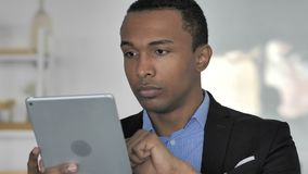 Close up Of Casual Afro-American Businessman Browsing Internet on Tablet. 4k high quality stock footage