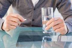 Close up of casual man holding a pill and glass of water Royalty Free Stock Photos