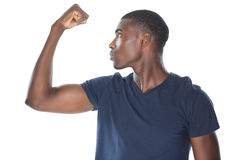 Close up of a casual young man flexing muscles Royalty Free Stock Photography