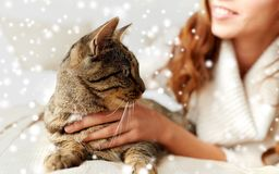 Close up of cat and woman in bed. Pets, animals, winter and people concept - close up of cat and woman in bed over snow Stock Photography