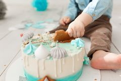 Close up of a caucasian birthday boy legs and arms while he destroys and smashes his cream cake with mint and white. Icing getting the sticky icing all over her Stock Photography