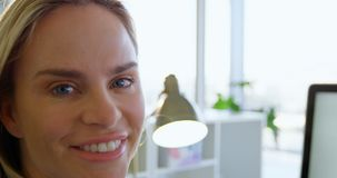 Close-up of Caucasian female fashion designer sitting at desk in office 4k stock video footage