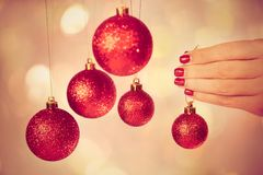 Woman holding New Year round balls ready to decorate tree. Close up of caucasian female hands with professional red manicure with glittering sparkles isolated on Royalty Free Stock Images