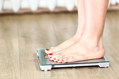Close up of Caucasian female legs standing on floor scales Stock Images