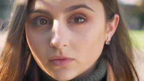 Close-up caucasian girl, portrait, casual, looking aside and then at camera straight, focused, thoughtful appearance. City background stock footage