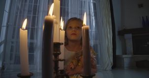 Close-up of Caucasian girl`s face behind candles. Weird child holding doll and looking around. Scare, fear, strangeness.
