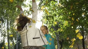 Close-up of caucasian grandmother and granddaughter tossing leaves in sunrays, jumping and spinning around. Two happy. Positive women having fun in the autumn stock footage