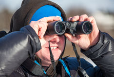 Man with binoculars looking far away Stock Photography