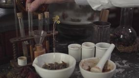 Close-up of Caucasian male hand touching ancient test tubes. Mortar and pestle standing at the table with different