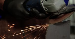 Male mechanic working in repair garage 4k. Close-up of Caucasian male mechanic working in repair garage. He is using angle grinder 4k stock video footage