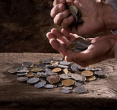 Close up of  caucasian old man's hands  and pile of old coins Stock Image