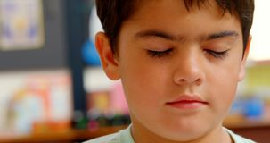 Close-up of Caucasian schoolboy sitting at desk in classroom at school 4k. Close-up of Caucasian schoolboy sitting at desk in classroom at school. He is closed stock footage