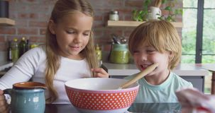 Siblings preparing cookie on worktop in kitchen at comfortable home 4k. Close-up of Caucasian siblings preparing cookie on worktop in kitchen at comfortable home stock footage
