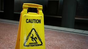 Close up of a caution sign near the train tracks of a subway station. 