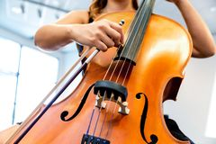 Close up of cello with bow in hands. Cellist playing violoncello musical instrument of orchestra stock photo