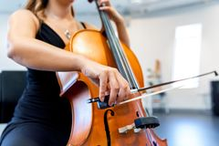 Close up of cello with bow in hands stock photography