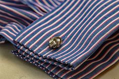 Close up of celtic knot design cuff link and fashionable stripy double cuff work shirt. Close up of celtic knot design cufflink and fashionable stripy double royalty free stock images