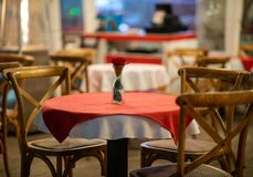 Close up of the centerpiece of a spanish restaurant table with red checkered tablecloth and wood chairs stock images