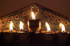 Close-up on ceramic hanukiah lit with 4 candles and shamash. Hanoukkah candlestick with olive oil Stock Photography