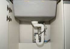 Ceramic kitchen sink installation with sink drain tubes plumbing. Stock Photography