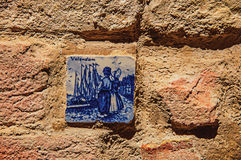 Close-up of ceramic tile attached to the wall in Colle di V-up of flowers on top wooden frame and blue sky at Colle di Val d`Elsa. Close-up of ceramic tile Royalty Free Stock Photography