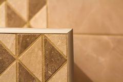 Close-up of ceramic tiles out corner with silver metal strip on the interior wall. Stock Images