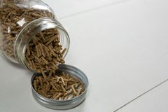 Cereal bran sticks spilling from glass jar Royalty Free Stock Image