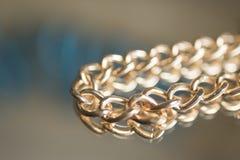 Close-up chain do ouro em um fundo do espelho Fotos de Stock