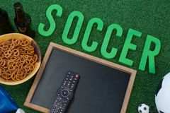 Chalkboard, snacks and football on artificial grass. Close-up of chalkboard, snacks and football on artificial grass royalty free stock photos